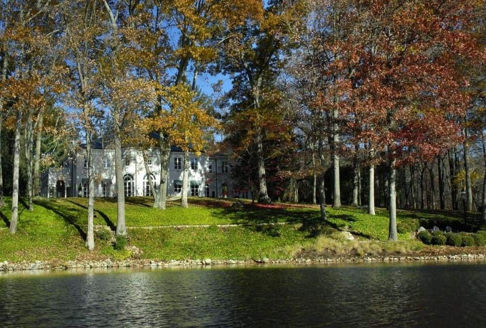 The back of the house has a large creek that adds to the charm of the area and landscaping filled with tall trees and grass. Images courtesy of Toptenrealestatedeals.com.