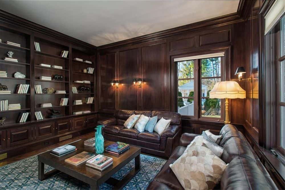 Gorgeous dark wooden built-in shelves are embedded into the wooden walls adorned with wall-mounted lamps and a sofa set of the same tone. Images courtesy of Toptenrealestatedeals.com.