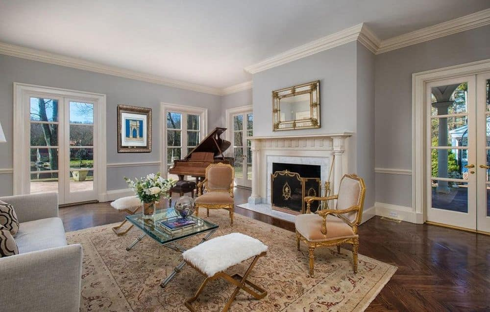 This living room has a couple of elegant arm chairs that has a classic design flanking the large fireplace with a white mantle. Images courtesy of Toptenrealestatedeals.com.