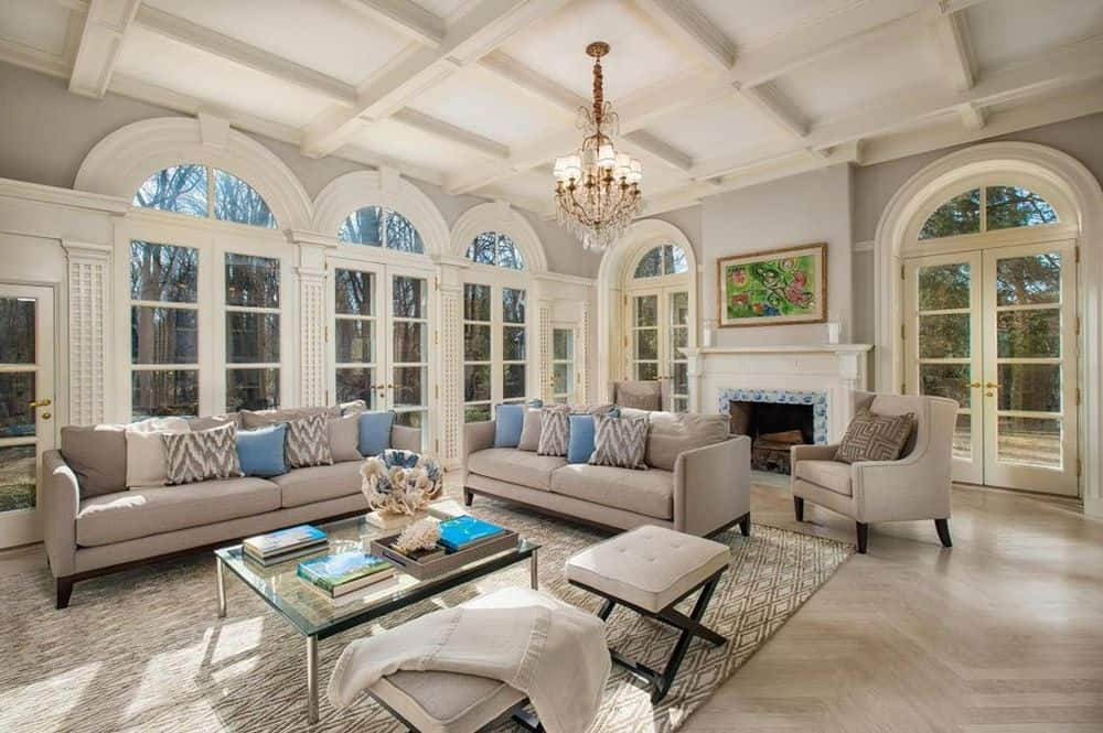 This living room has a tall coffered ceiling paired with a chandelier and a row of tall arched windows that bring in an abundance of natural lighting for the beige sofa set. Images courtesy of Toptenrealestatedeals.com.