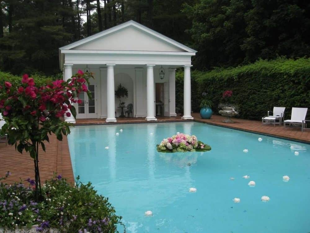 The large pool of the backyard is surrounded by terracotta walkways and tall hedges of shrubs for maximum privacy. Images courtesy of Toptenrealestatedeals.com.