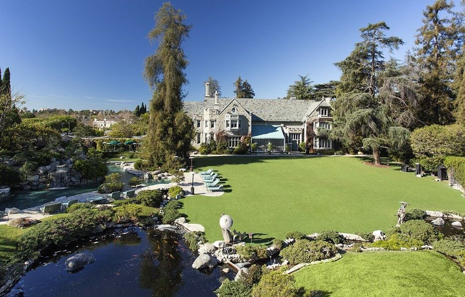 The is the massive backyard of the mansion with wide lawns of well-maintained grass adorned with tall mature trees. Images courtesy of Toptenrealestatedeals.com.