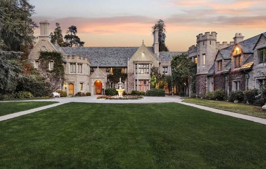 This is the front view of the world famous Playboy Mansion with a large lawn of grass with walkways leading to a courtyard with a fountain the middle. This serves as a nice foreground for the large mansion with stone gray exteriors and a castle-like vibe with turrets. Images courtesy of Toptenrealestatedeals.com.