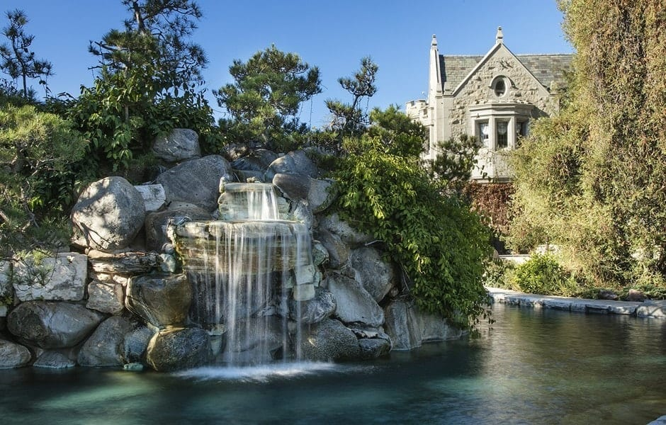 This is a gorgeous large pool incorporated with a charming landscaping designed to imitate natural formations including the charming stone falls on the far side topped with tall trees. Images courtesy of Toptenrealestatedeals.com.