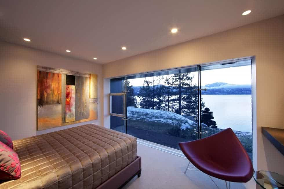 This is the guest bedroom with a wide glass wall across from the simple cottage bed adorned with a modern red chair at the corner for a reading area. Images courtesy of Toptenrealestatedeals.com.