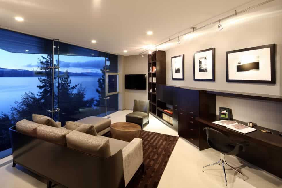 The Contemporary-style mansion also has a den and office with bright walls and ceiling contrasted by the glass wall on one side. This room has a comfortable sofa and a built-in long wooden desk on the side for an office area. Images courtesy of Toptenrealestatedeals.com.