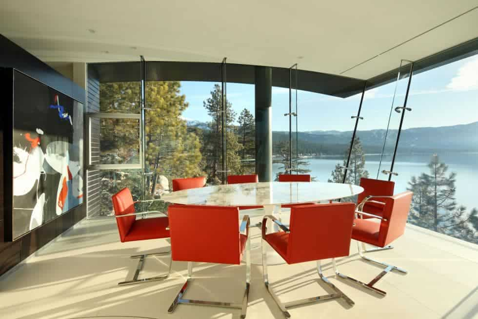 This beautiful dining area has a large round dining table surrounded by bright orange modern chairs and has a sweeping view of the lake and treetops through the glass walls. Images courtesy of Toptenrealestatedeals.com.