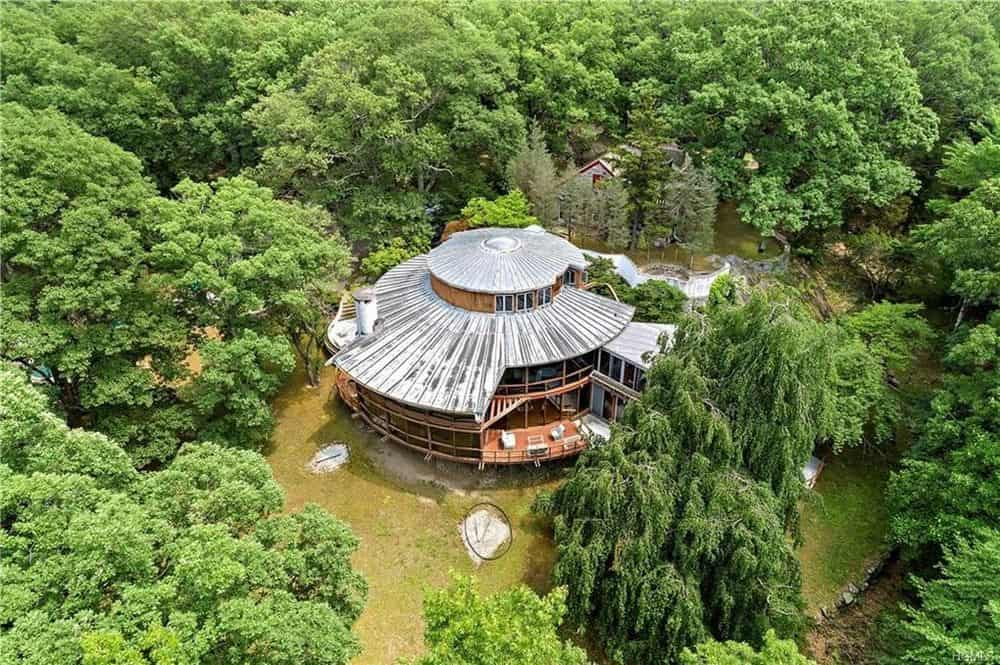 This aerial view of the house showcases its unique round UFO-like shape and the surrounding tall trees that bring privacy and isolation to the house. Images courtesy of Toptenrealestatedeals.com.