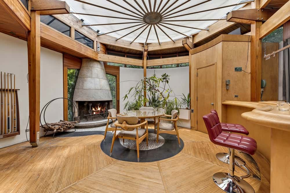 The warm stone fireplace gives an additional charm to this homey dining room with an intimate round wooden dining set in the middle of the hardwood flooring under a frosted glass ceiling. Images courtesy of Toptenrealestatedeals.com.