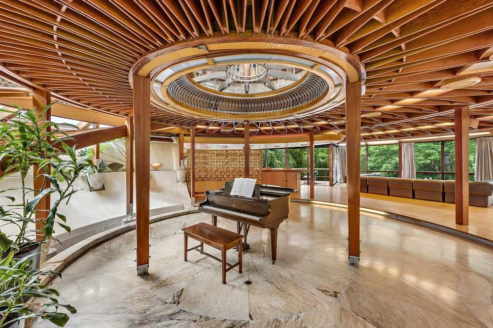 This is a closer look at the piano in the middle of the round marble flooring surrounded by thin wooden pillars that support the gorgeous intricate wooden ceiling with exposed beams. Images courtesy of Toptenrealestatedeals.com.