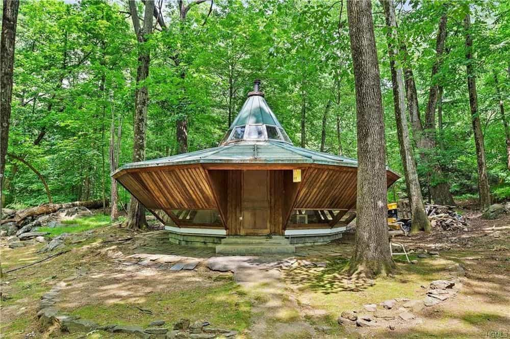 This is one of the smaller houses in the compound with a unique UFO-like shape surrounded by tall trees and a natural landscape. Images courtesy of Toptenrealestatedeals.com.