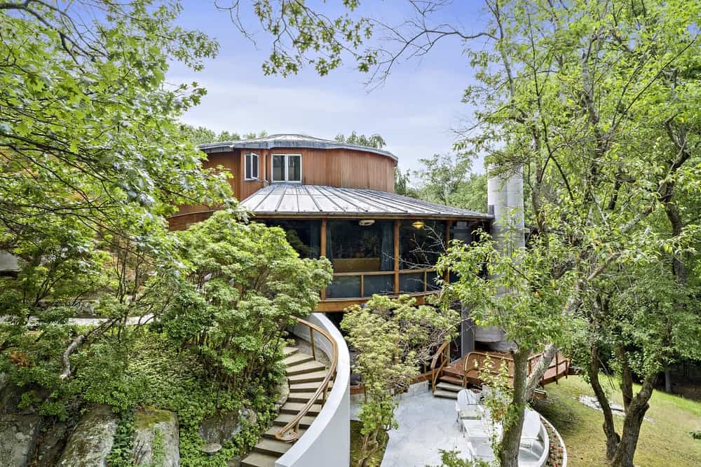 This is the front view of the large house with a lovely outdoor curved staircase leading to the house adorned with tall trees. Images courtesy of Toptenrealestatedeals.com.
