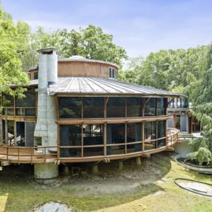 This is the main house of the compound named Mother Ship with a large two-story UFO-shaped structure that has glass walls and a huge chimney on the side surrounded by mature tall trees and grass lawns. Images courtesy of Toptenrealestatedeals.com.