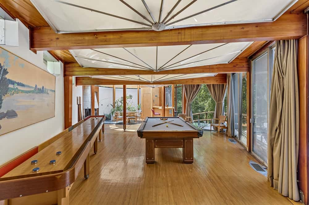 The game room has a large pool table in the middle of the hardwood flooring topped with a frosted glass ceiling supported by exposed wooden beams. Images courtesy of Toptenrealestatedeals.com.