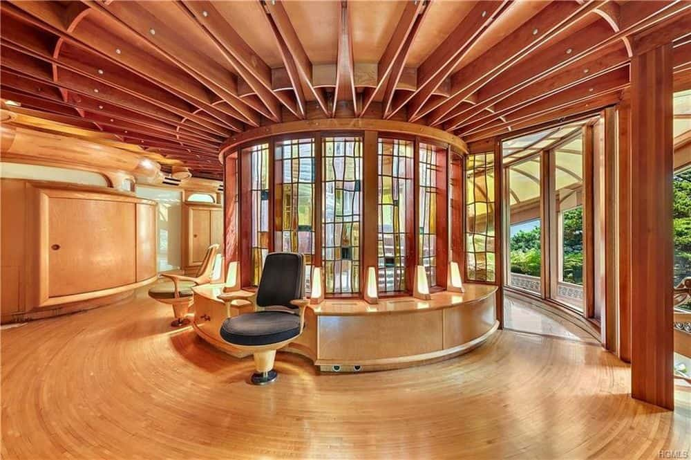 The second floor hall has a large central circular structure in the middle fitted with stained glass and built-in arm chairs for a unique spaceship-like look. Images courtesy of Toptenrealestatedeals.com.
