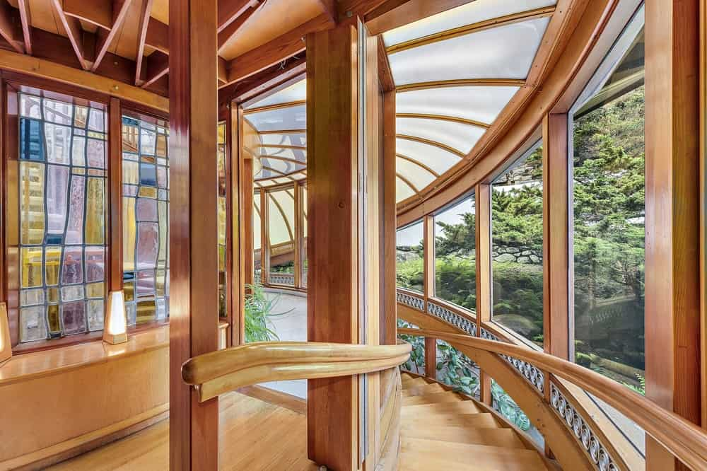 This is the view from the second floor landing of the house featuring the wooden curved staircase matching with the handles and ceiling that is fitted with frosted glass panels to filter the natural lights. Images courtesy of Toptenrealestatedeals.com.