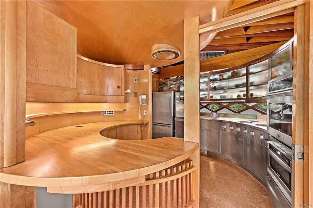 This is the charming kitchen dominated by the wooden elements of the ceiling, hardwood flooring and the built-in wooden curved counted with a wooden column.
