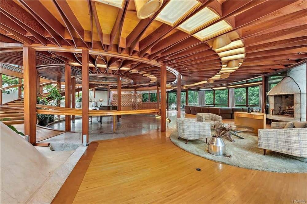 This is the view from the other side of the living room featuring the large circular great room that has wide hardwood flooring and gorgeous ceiling with exposed wooden beams. Images courtesy of Toptenrealestatedeals.com.