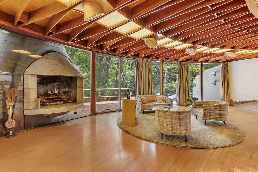 This gorgeous and spacious living room has comfortable woven wicker sofas that matches well with the hardwood flooring and ceiling with exposed beams. These are then warmed by a fireplace on the side of the glass walls. Images courtesy of Toptenrealestatedeals.com.