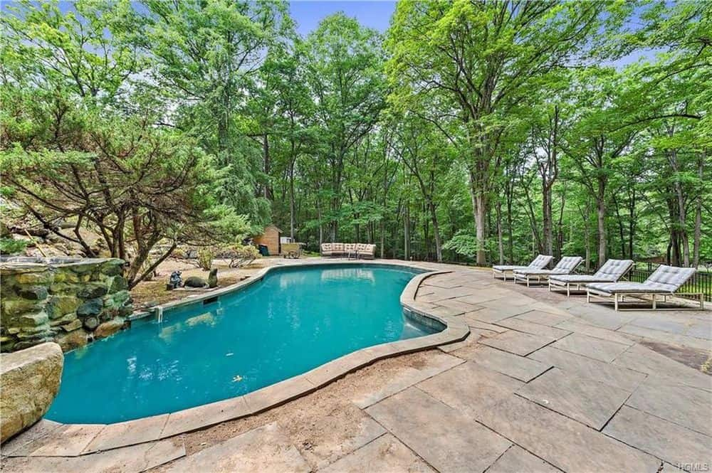 The property has a large pool surrounded by stone slab walkways and tall trees that provide shade and privacy as well as a nice background. Images courtesy of Toptenrealestatedeals.com.