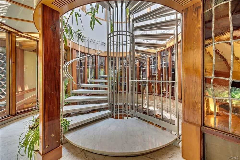 This is a closer look at the spiral staircase with an entryway flanked by wooden columns and decorated with leaves to create a natural and homey aesthetic. Images courtesy of Toptenrealestatedeals.com.