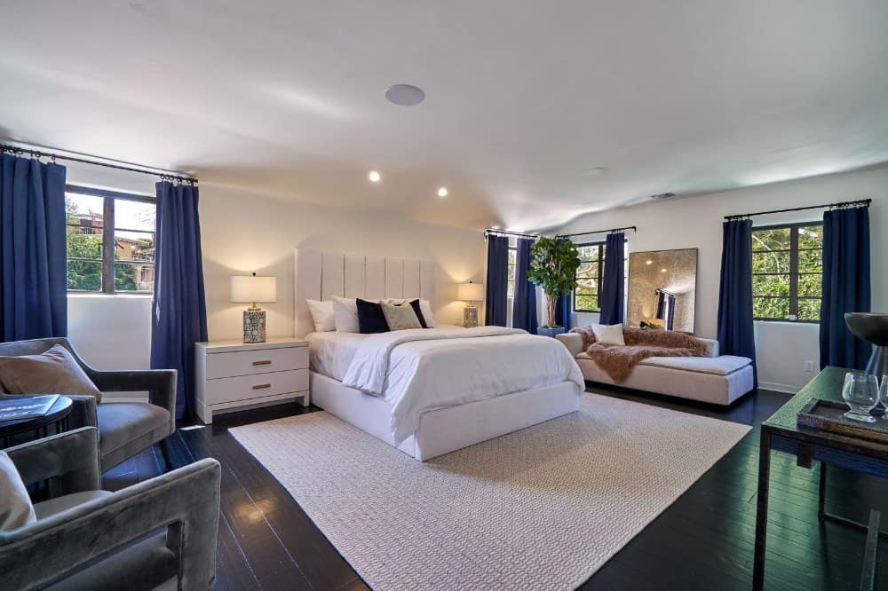 Large primary bedroom suite with a classy bed set and a pair of gorgeous gray arm chairs on the side. Images courtesy of Toptenrealestatedeals.com.