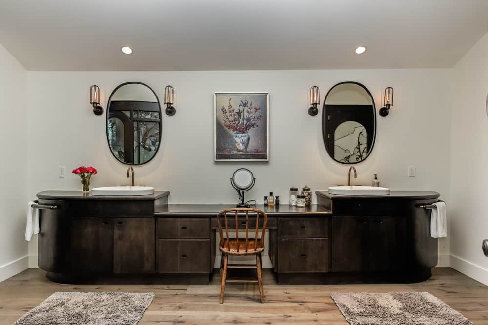 This large bathroom has a wide two-sink dark wooden vanity that makes it stand out against the beige walls and ceiling. These are then topped with wall-mounted mirrors flanked by wall-mounted lamps with a painting in the middle. Images courtesy of Toptenrealestatedeals.com.