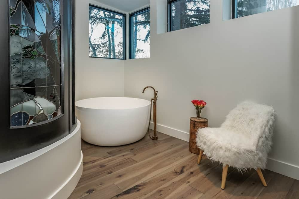 This bathroom has a round corner bathtub placed on the corner below the row of windows. Across from this is the modern walk-in shower area that matches the tone of the walls. Images courtesy of Toptenrealestatedeals.com.