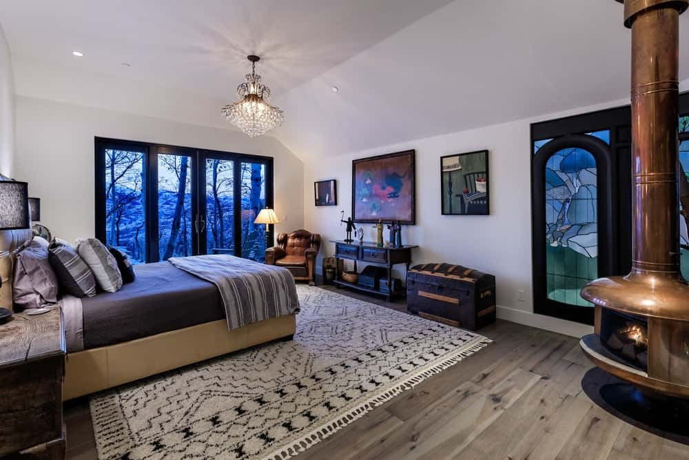 This bedroom has a crystal chandelier that complements the beige ceiling that blends well with the beige walls. The beige walls go well with the beige platform bed with a cushioned headboard. The highlight of this room has got to be the gorgeous stained glass windows that depict mountain scenes to match the scenery outside the glass windows on the far side. Images courtesy of Toptenrealestatedeals.com.