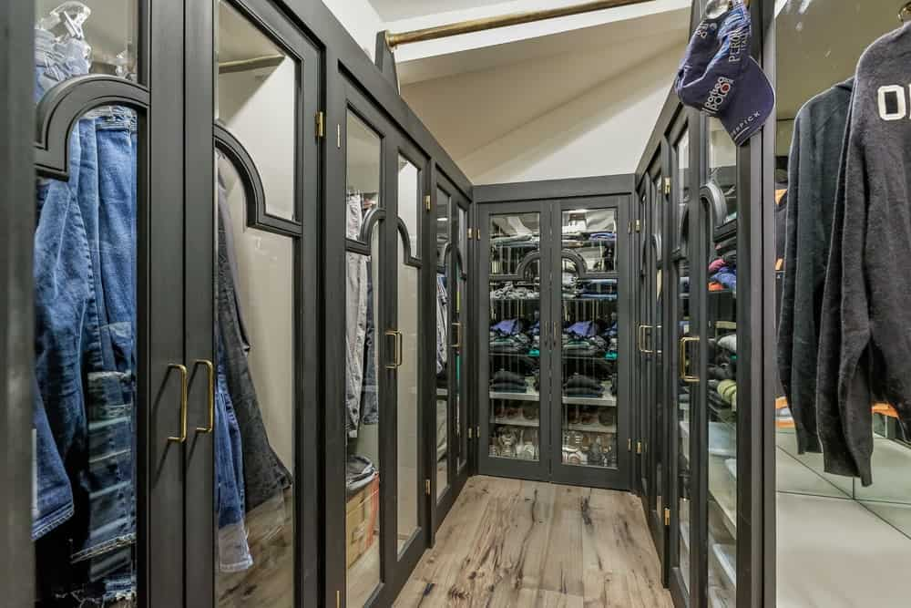 The walls of this narrow closet are lined by the glass-covered cabinets with a dark gray tone that works quite well with the hardwood flooring and the beige walls. Images courtesy of Toptenrealestatedeals.com.