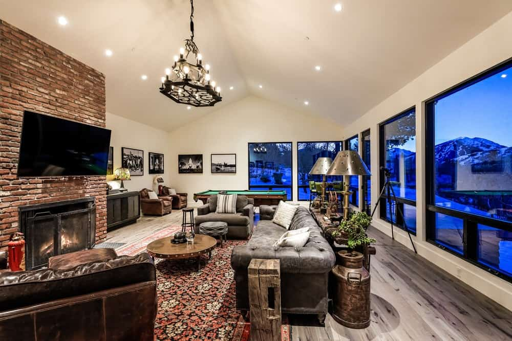This large room houses both the family room and the game room under the same beige cathedral ceiling that hangs a majestic two-tier chandelier over the family room that is warmed by a red brick fireplace. Images courtesy of Toptenrealestatedeals.com.