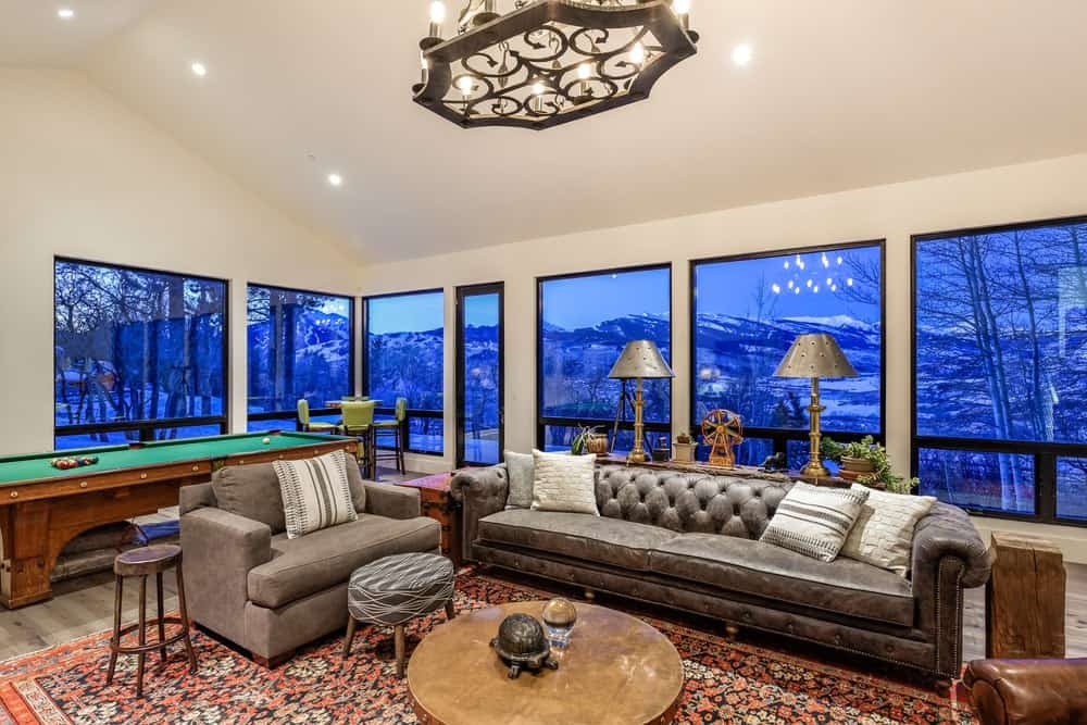 The red brick fireplace is matched well by the red patterned area rug of the family room that is complemented by comfortable gray sofas paired with a wooden coffee table. Images courtesy of Toptenrealestatedeals.com.
