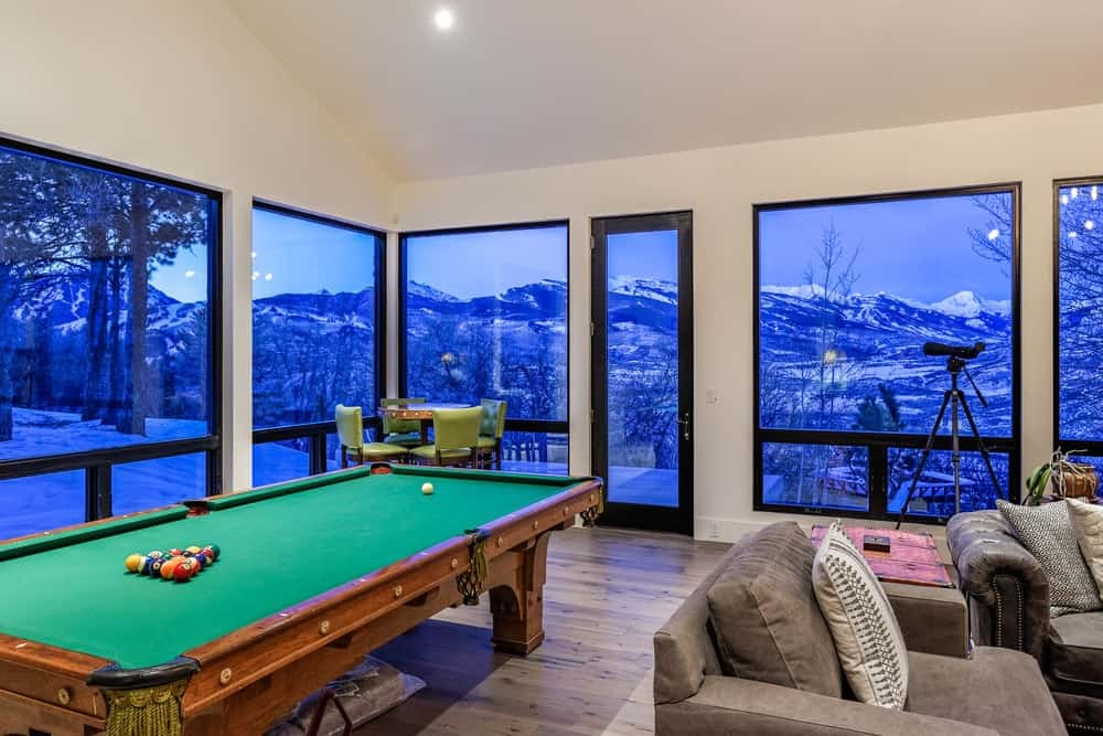 This game room area is right beside the family room sharing the warmed of the fireplace. It has a large pool table surrounded by a bright row of windows giving you a wonderful view of the mountains. Images courtesy of Toptenrealestatedeals.com.