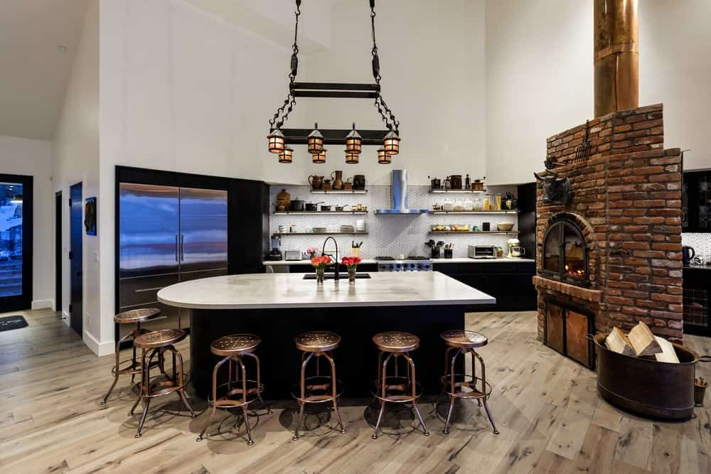 The charming kitchen has a large kitchen island that has a black hue to contrast the brass stools surrounding the breakfast bar. This is matched by the stainless steel fridge that is also contrasted by the back wall the houses it. The highlight of this kitchen is the freestanding red brick fireplace that stands out against the hardwood flooring. Images courtesy of Toptenrealestatedeals.com.