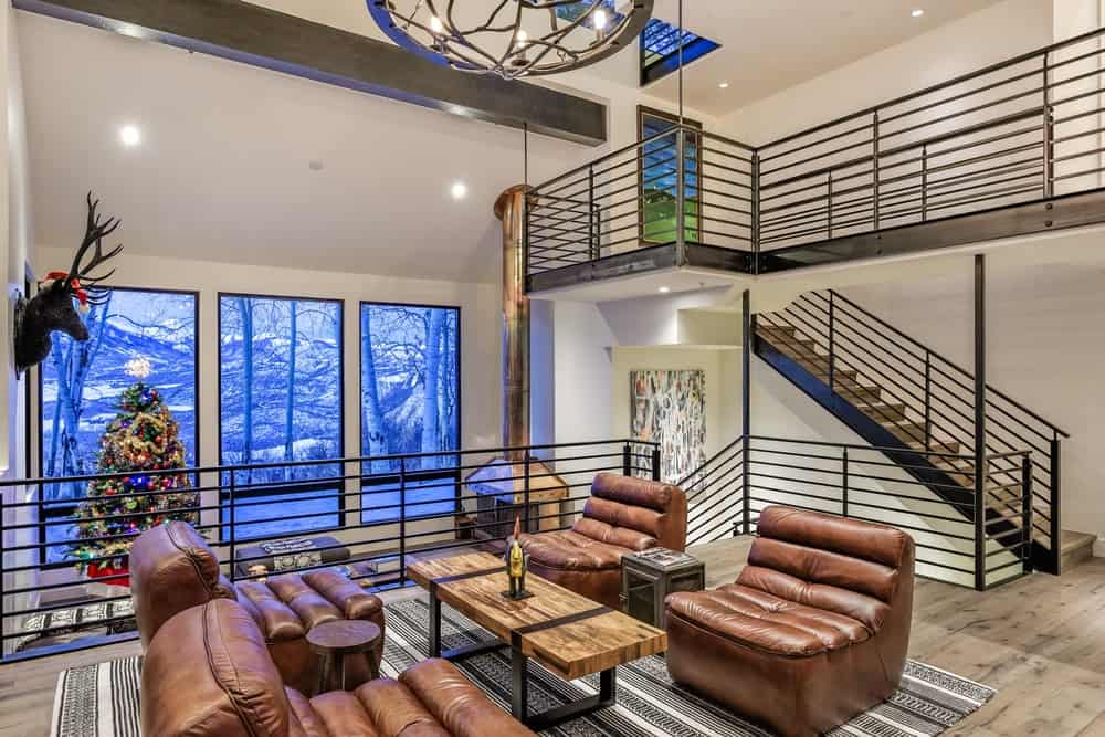 On the far side, you will see that there is a comfortable area by the row of tall windows adorned with a cheery Christmas tree on the corner. This area is warmed by the brass fireplace that balances the snowy scenery afforded by the large windows. Images courtesy of Toptenrealestatedeals.com.