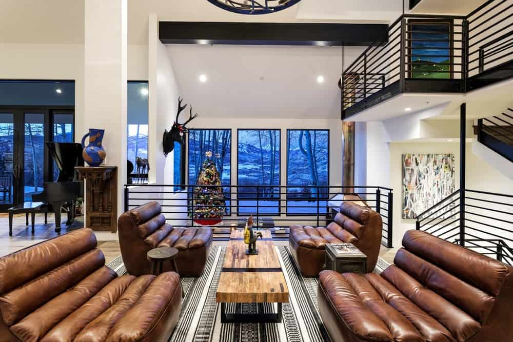 The area has four comfortable brown leather cushioned chairs that are paired with side tables and a rectangular wood-top coffee table in the middle over a striped gray area rug. Images courtesy of Toptenrealestatedeals.com.