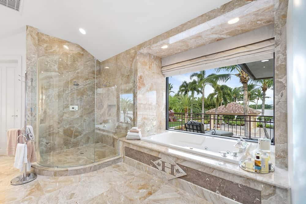 This is the luxurious and charming primary bathroom with the same marble on its flooring, walls and bathtub inlay. The bathtub is placed under a large glass window beside the glass-enclosed shower area. Images courtesy of Toptenrealestatedeals.com.