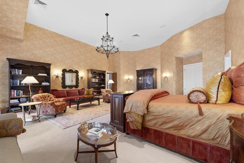 The primary bedroom of the mansion has a large sitting area across from the gorgeous bed with a dresser at its foot matching the shelves of the sitting area. Images courtesy of Toptenrealestatedeals.com.