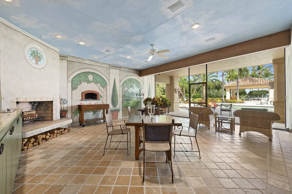 This is the al fresco dining area with charming terracotta flooring tiles, sky blue ceiling and a large wood-burning pizza oven on the far wall. Images courtesy of Toptenrealestatedeals.com.