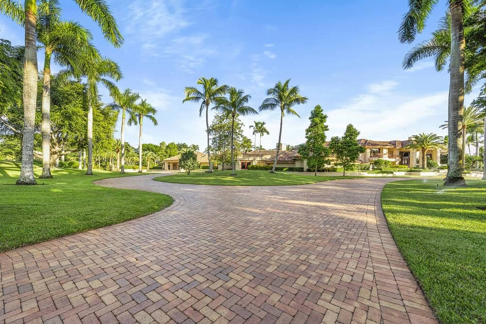 This beautiful and wide driveway is made of earthy bricks and complemented by the lush landscaping surrounding it filled with green grass and tall palm trees. Images courtesy of Toptenrealestatedeals.com.