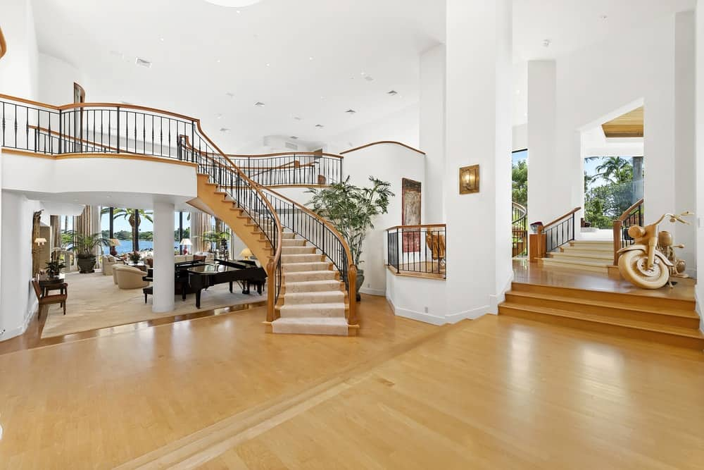 The foyer continues on to this large open receiving area that has a wide hardwood flooring to pair with the staircase. Images courtesy of Toptenrealestatedeals.com.