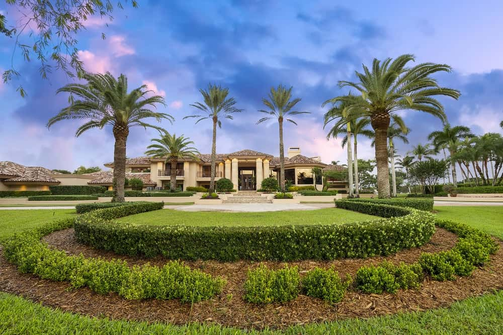 This is the gorgeous and large front yard of the mansion with tall tropical palm trees paired with well-maintained hedges and grass lawns to complement the earthy tones of the house exterior. Images courtesy of Toptenrealestatedeals.com.