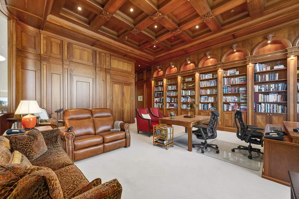 This is the lush and luxurious library with rich wooden coffered ceiling to match the wooden walls that has embedded built-in shelves with wall-mounted lamps. Images courtesy of Toptenrealestatedeals.com.