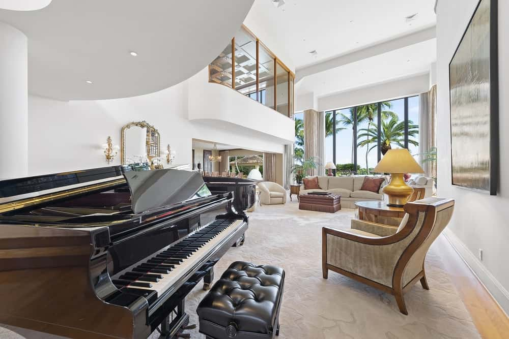 Underneath one of the indoor balconies is a grand piano just beside the spacious living room that has a soaring ceiling paired with tall glass walls. Images courtesy of Toptenrealestatedeals.com.