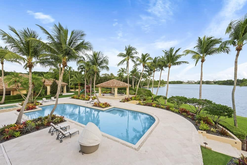 This is the beautiful view that is afforded by the second floor terrace facing the back of the house. Here you can see the palm trees, pool and the water scenery beyond. Images courtesy of Toptenrealestatedeals.com.