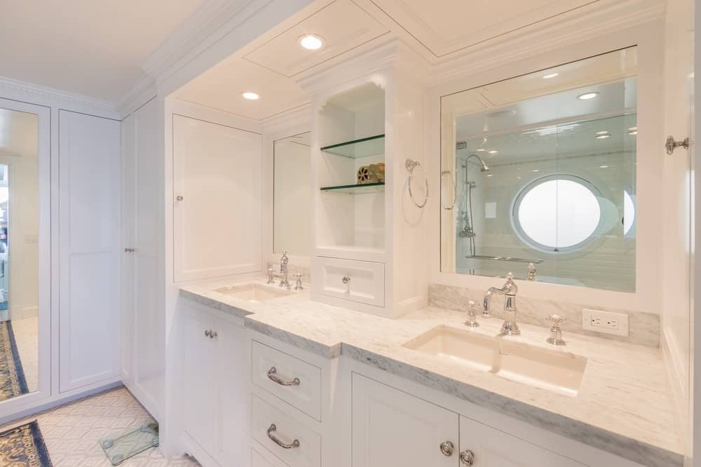 The bathroom has a large luxurious vanity with two sinks, elegant white cabinets and drawers topped with built-in mirrors and recessed lights. Images courtesy of Toptenrealestatedeals.com.