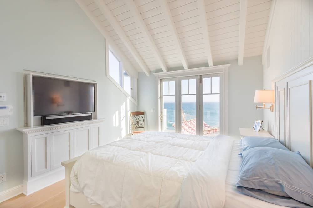 This is a simple and charming bedroom with a bright and relaxing feel to its white walls and ceiling contrasted by the TV across from the large bed. . These are then contrasted by the TV across from the Images courtesy of Toptenrealestatedeals.com.
