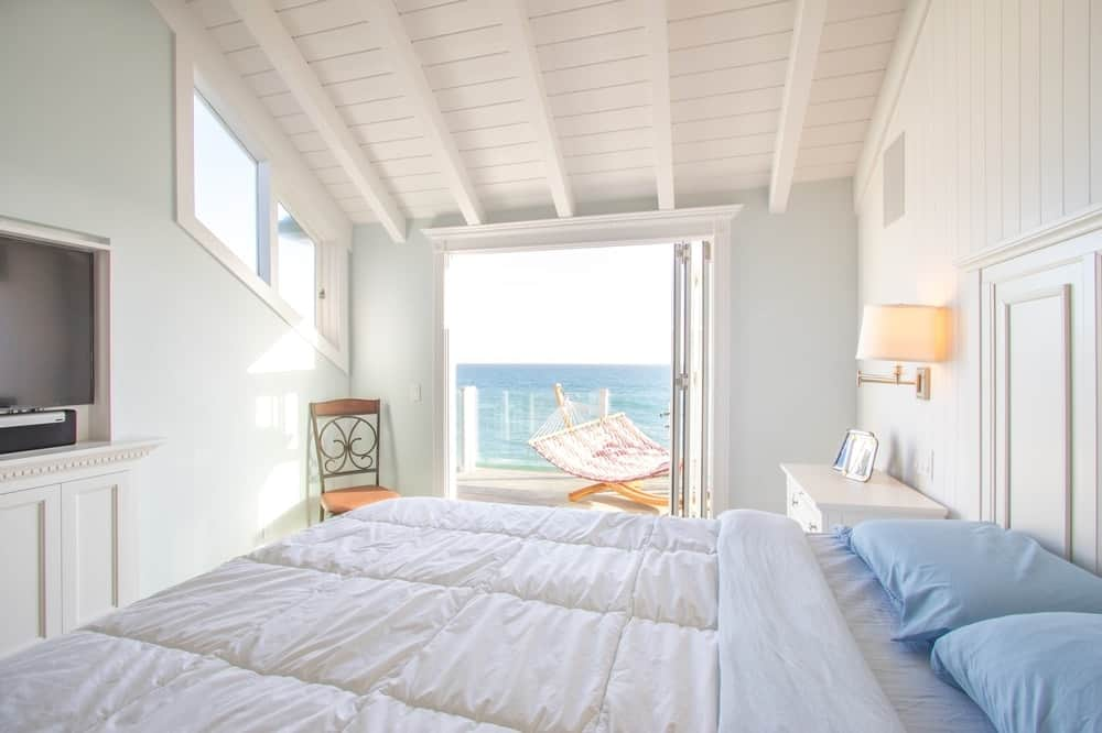 This is the view of the bedroom with the accordion balcony doors opened. This brings in an abundance of natural lighting to complement the bright white shed ceiling with wooden exposed beams. Images courtesy of Toptenrealestatedeals.com.