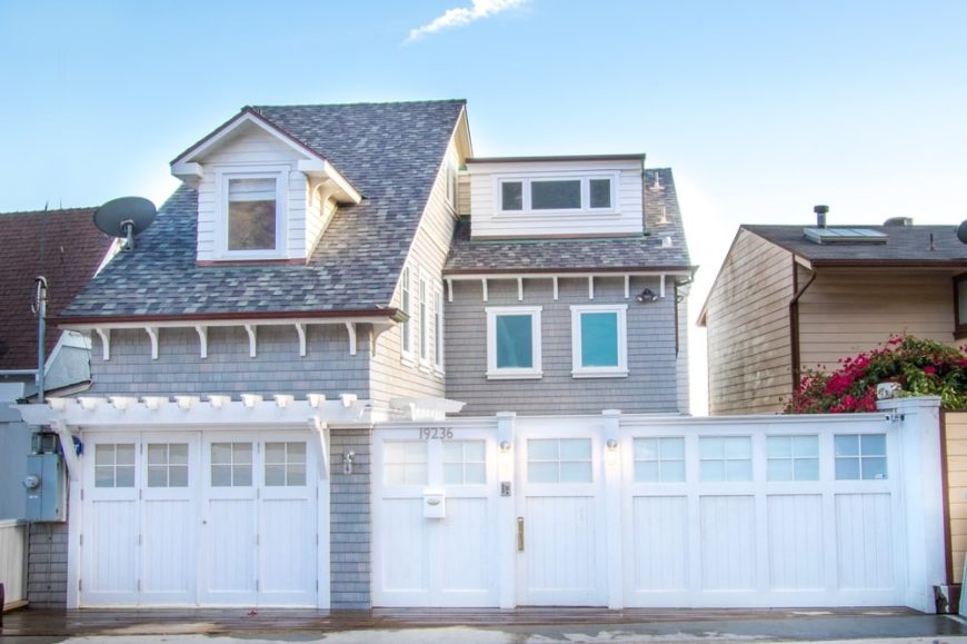 This is the front view of the beautiful beach house that has a tall white gate for privacy and it also matches with the garage doors as well as the dormer windows that stand out against the light gray roof. Images courtesy of Toptenrealestatedeals.com.