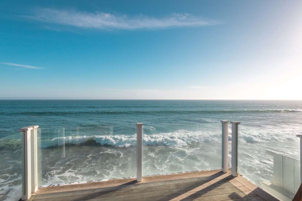 This is the beautiful scenic view of the ocean from the vantage of the balcony that has a wooden deck and glass railings to maximize the view. Images courtesy of Toptenrealestatedeals.com.